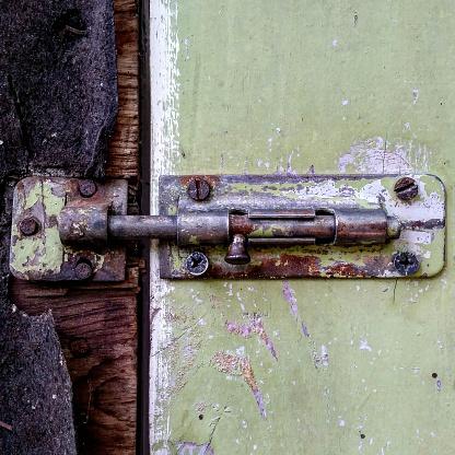 A picture of an old, rusty door latch on a peeling door