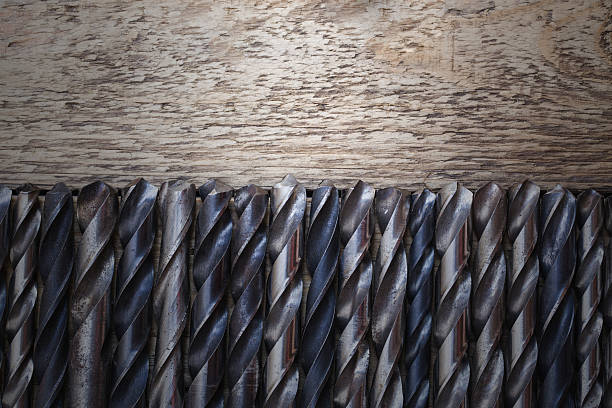 old rusty drill bits on wooden table - horse bit stock photos and pictures