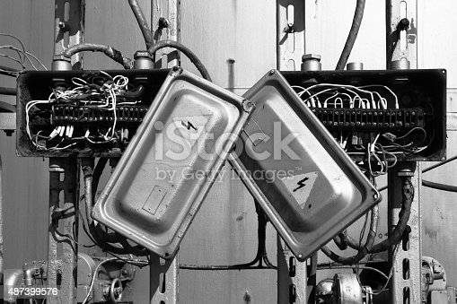 istock Old rusty electric transformer box with wires 487399576