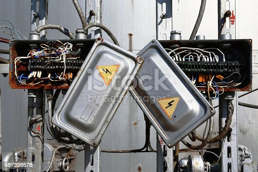 istock Old rusty electric transformer box with wires 487399578