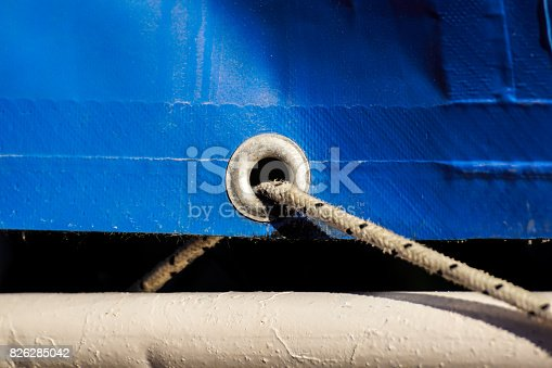 istock old rusty eyelets on an aged blue coated plastic canvas 826285042