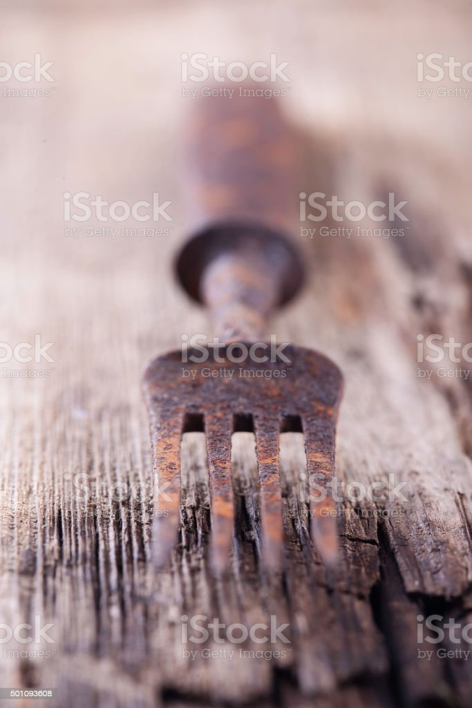 old rusty fork on a wooden Board closeup stock photo