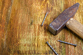 Old rusty hammer and three steel nails lie on a scratched wooden table. Copy space for text. Selective focus. Home work concept. Close-up.