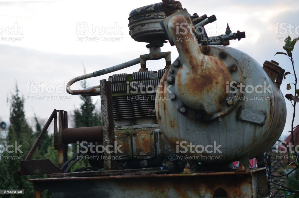 Old rusty industrial engine standing on the street. stock photo