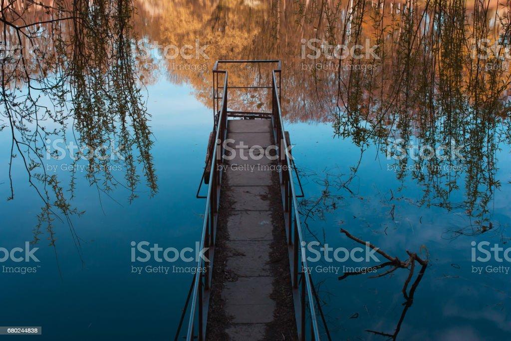 Old, rusty, iron bridge on the lake, sea stock photo