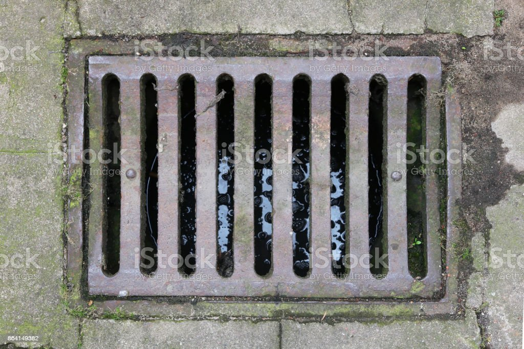 Old rusty iron grille of the rain sewer system of the city. royalty-free stock photo