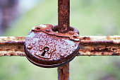 Rusty old iron chain with padlock attached to a wooden door