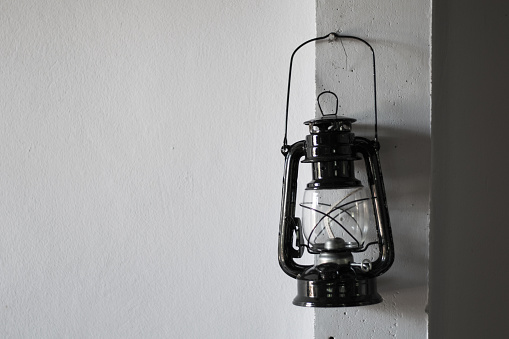 old rusty kerosene lamp on the white wall black and white