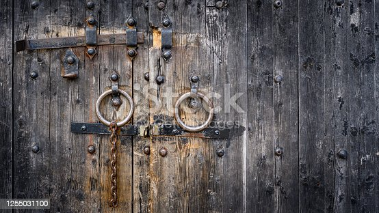 Old wooden gates detail with rusty bolt and lock.