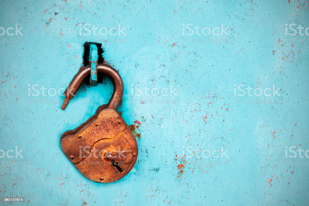 Old rusty lock without a key on a blue background Old rusty lock without a key on a blue background. Antique Stock Photo