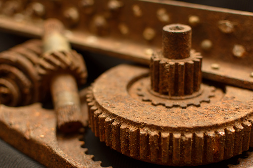 A photo of old and rusted parts of the mechanism of a WWII airplane close-up with a shallow depth of field