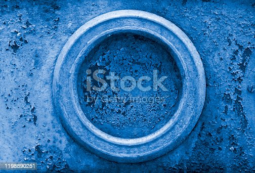 istock Old rusty metal background with cracked paint and round element. Textured background toned in Classic Blue color. 1198890251