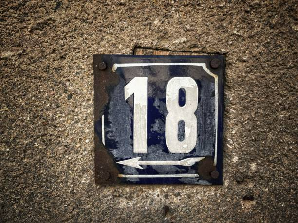 Old rusty metal sign with number 18 hung on a brick wall stock photo
