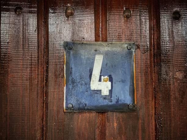 Old rusty metal sign with number 4 hung on a wooden fence stock photo