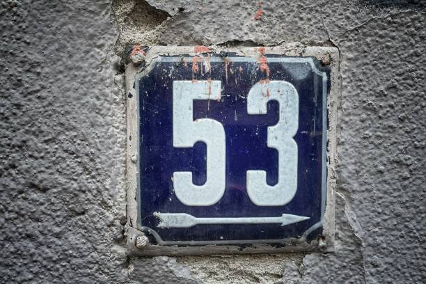 Old rusty metal sign with number 53 hung on a brick wall stock photo