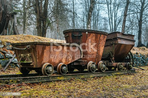 Old and rusty mining train standing on some old track in a mining area in Sweden, on a foggy day with autumn colors