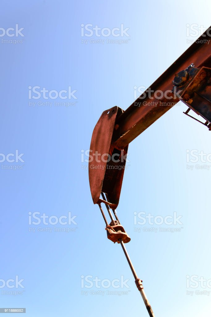 old rusty oil derrick in sunlight with blue sky stock photo