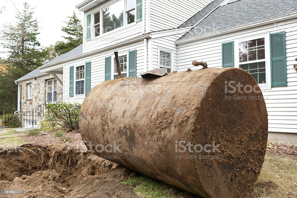 Old rusty oil tank in front of house stock photo