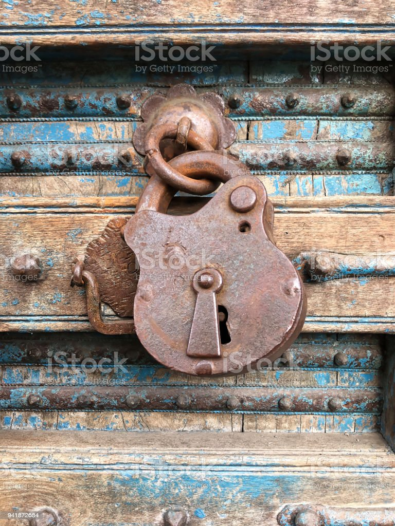 Old rusty padlock hanging on a dilapidated wooden door stock photo