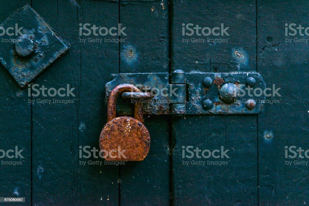 Old rusty padlock on wooden doors, old green destroyed door,safety stock photo