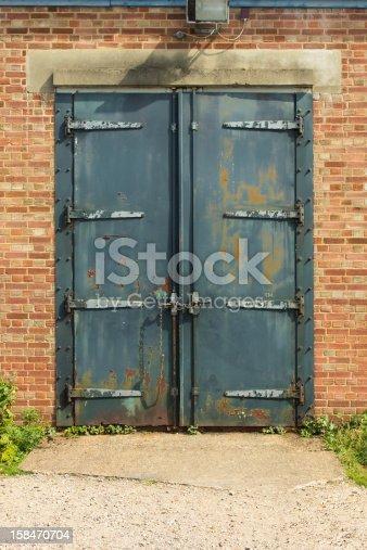 istock Old rusty padlocked blue metal door 158470704