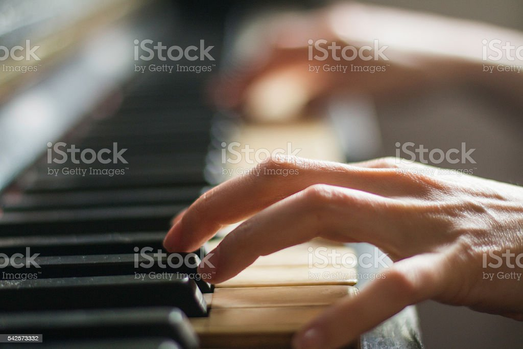 Old rusty piano, selective focus, woman's hands on keyboard stock photo