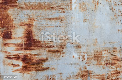 924754302istockphoto Old rusty piece of banner .Textured empty  abandoned street  advertising  panel with white peeling paint 1140404705