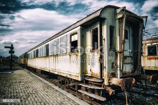 vintage looking photo of rusty old railcars and trains on an abandoned rail platform