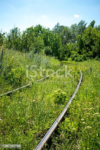 old abandoned railway track and a green summer meadow. Village landscape
