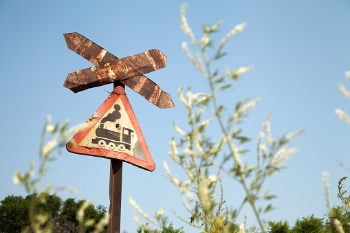 Old rusty road sign with train picture - railroad crossing