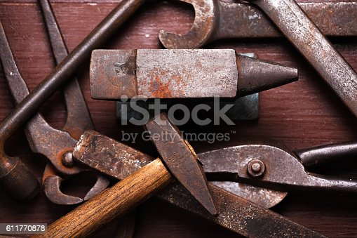 istock Old rusty rugged anvil and other blacksmith tools. 611770878
