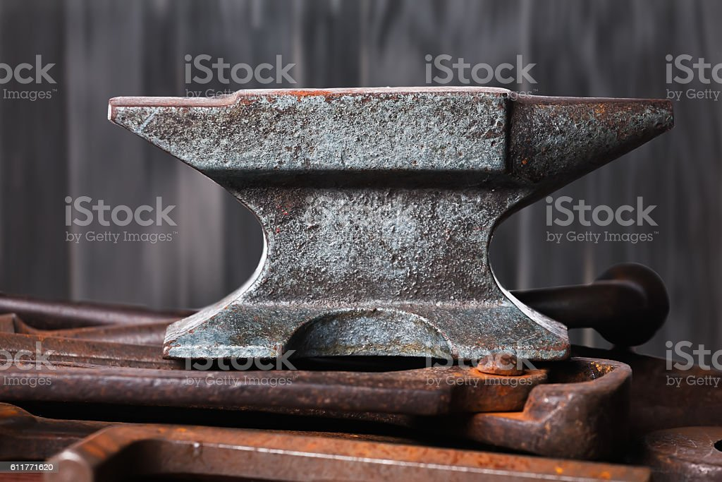 Old rusty rugged anvil on top of other blacksmith tools. stock photo