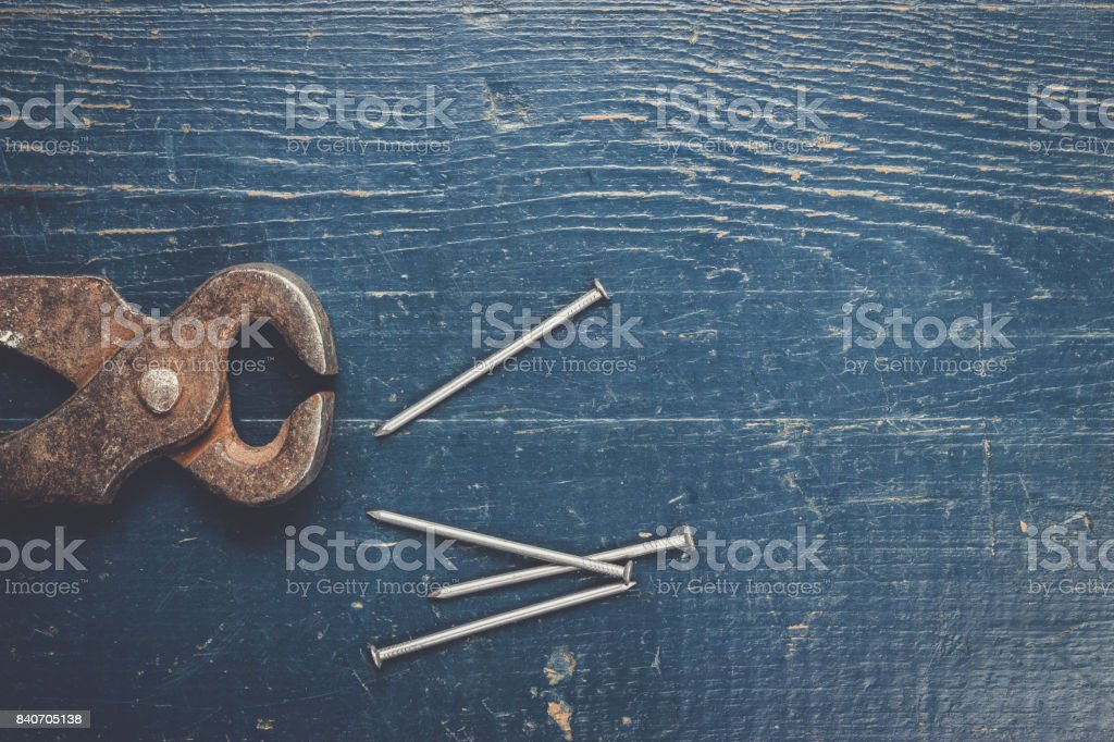 old rusty tongs on blue table stock photo
