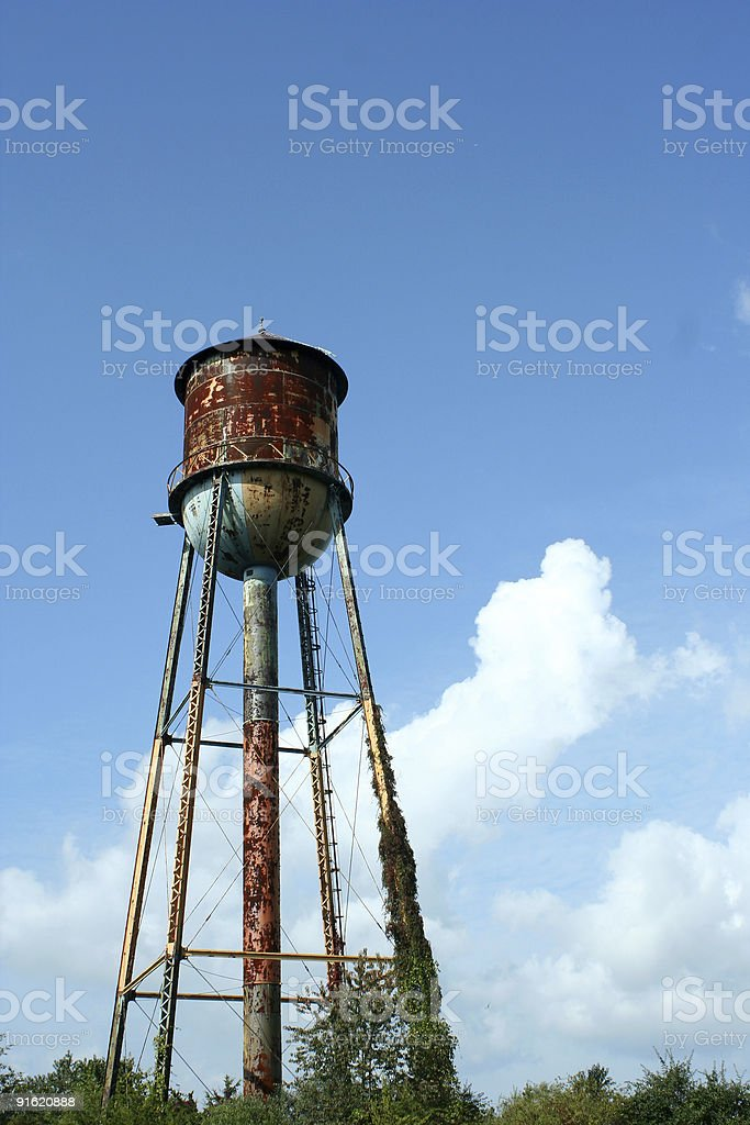Old rusty watertower against blue sky stock photo