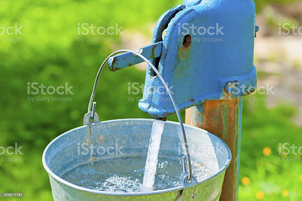 old rusty wheel and a bucket of clean water stock photo