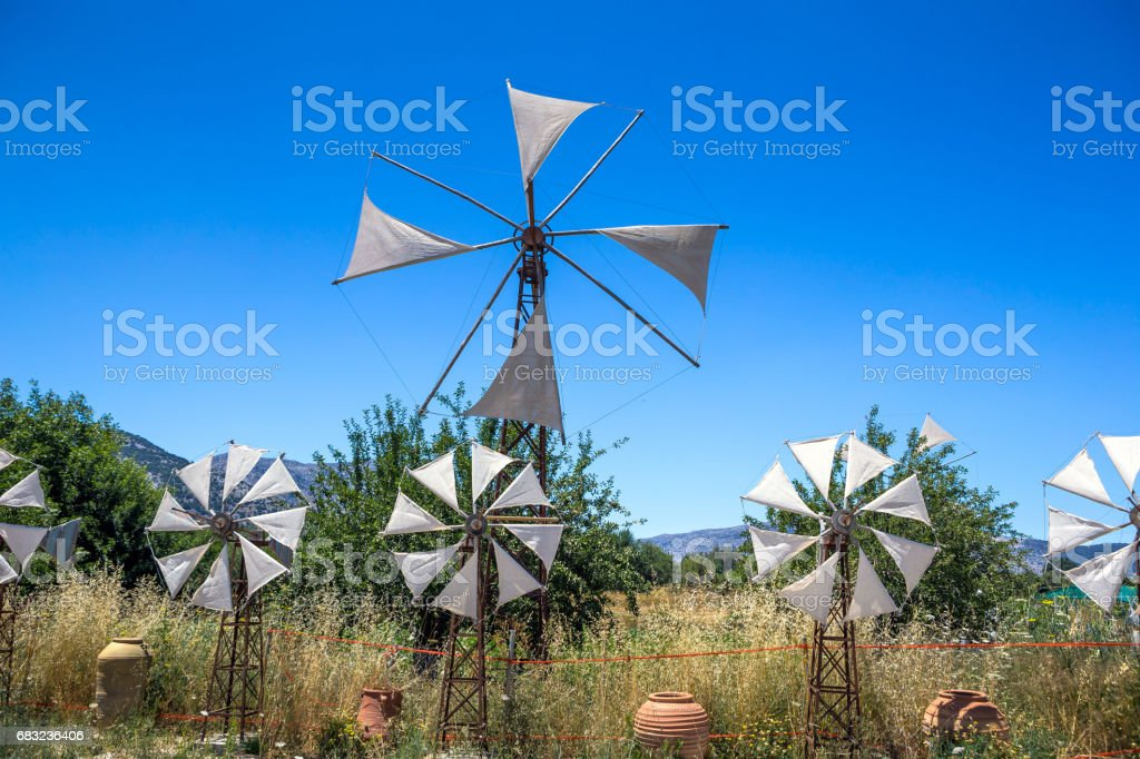 Old rusty windmills on the field. Agriculture in Greece, Crete 免版稅 stock photo
