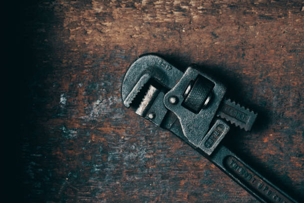 Old Rusty Wrench An antique wrench on an old wood surface adjustable wrench stock pictures, royalty-free photos & images