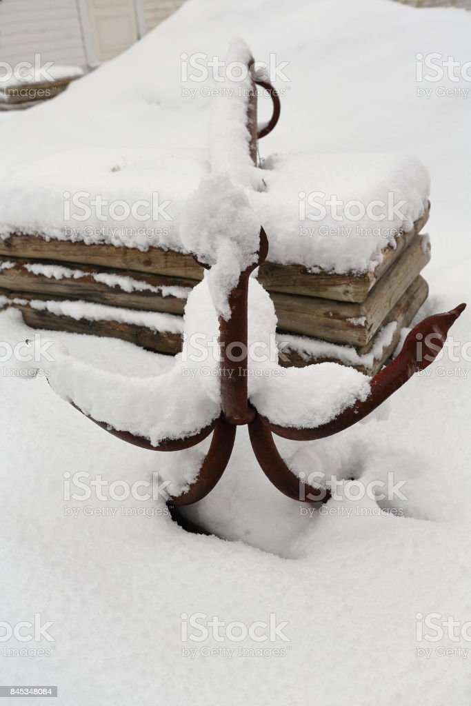 Old rusty-five tined grapnel anchor on snowy ground. Hamnoy-Reine-Lofoten-Norway. 0387 stock photo