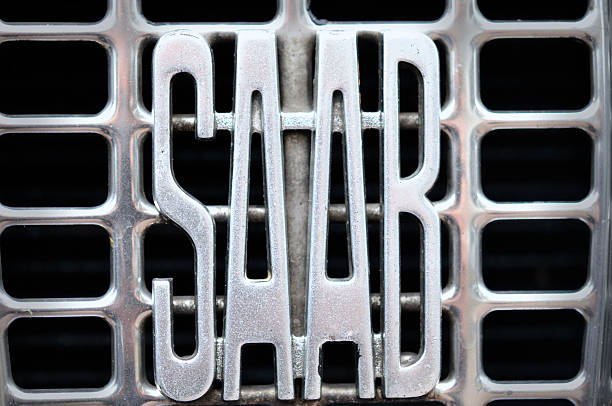 Old Saab logo Kampen, The Netherlandsd - July 9, 2011: Old Saab logo in the grille of a classic Saab 95 car. Saab Automobile AB, better known as Saab (Svenska Aeroplan Aktiebolaget) is a Swedish car manufacturer owned by Dutch automobile manufacturer Swedish Automobile NV, formerly Spyker Cars NV. saab stock pictures, royalty-free photos & images