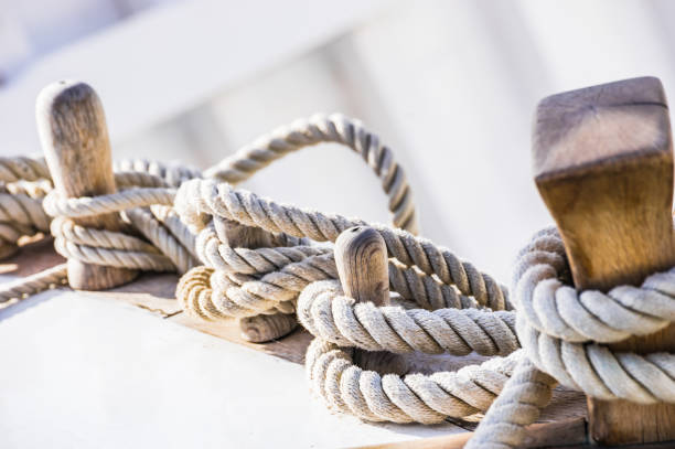 Old sailboat, detail closeup of wooden cleats with nautical moored ropes Close-up of moored ropes on wooden cleats on old sailing boat mooring stock pictures, royalty-free photos & images