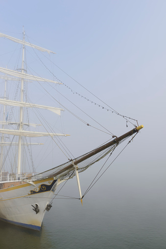 Old traditional sailing ship moored at the IJssel quay in Kampen during a misty morning at the river. The ship is used for tours along the lakes in the Netherlands and the North Sea.