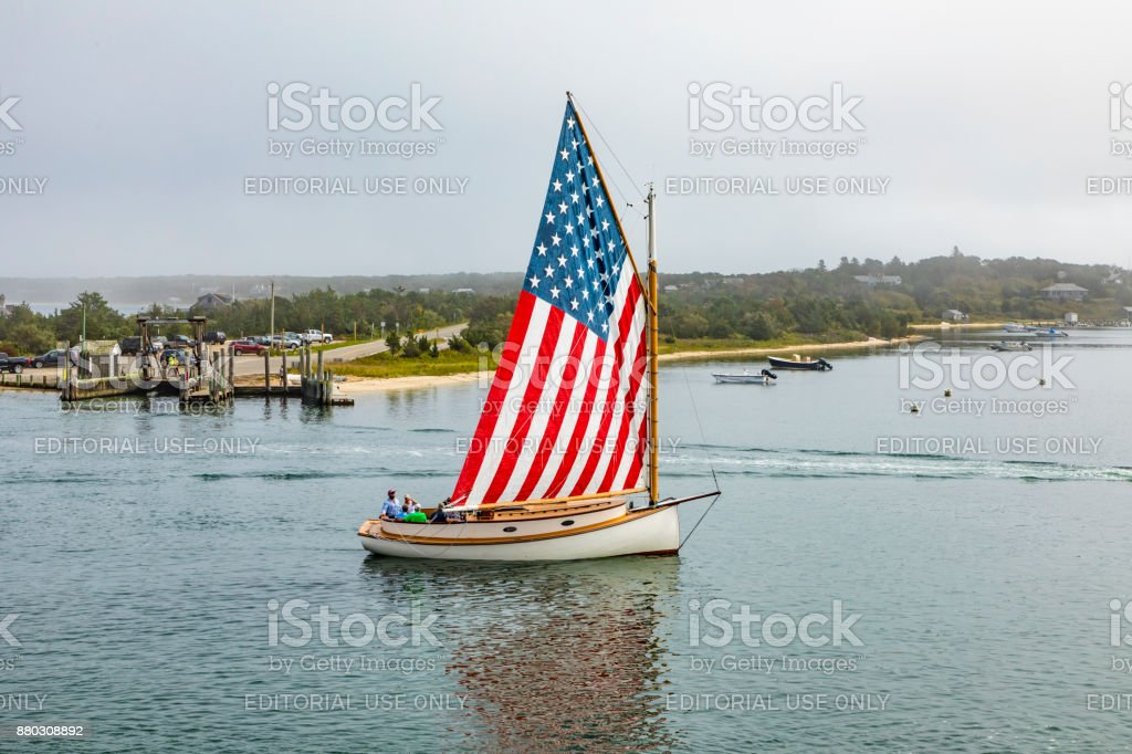 old sailing ship with stars and stripes sails enter the harbor of Edgartown stock photo