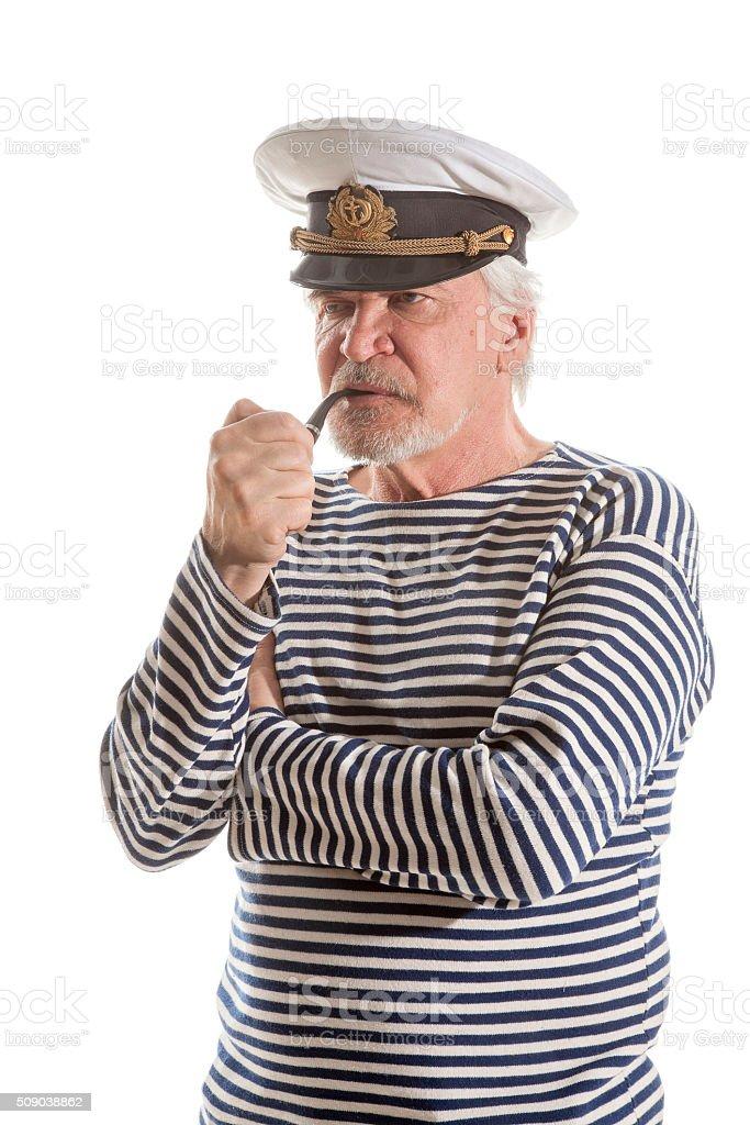Old sailor man smokes pipe stock photo