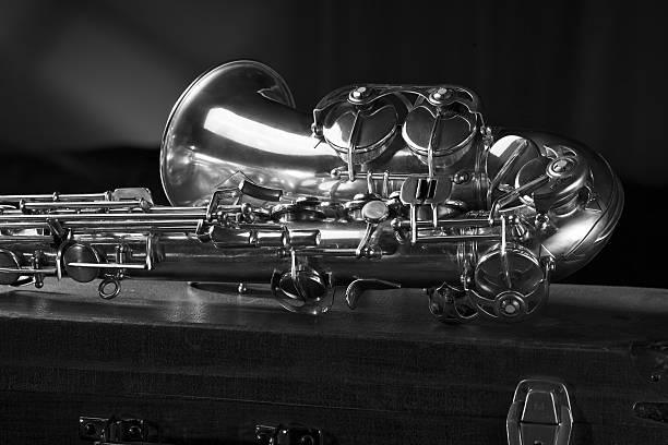 Old saxophone lying on the suitcase. stock photo