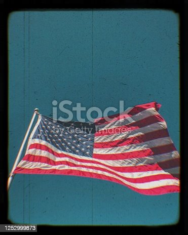 Vintage recreation of a beautiful American flag, waving proudly in the blue sky, with a digital enhancement overlay added in post production to make the photograph appear like retro film screen.  Photograph taken on a farm in Amberg, Wisconsin.