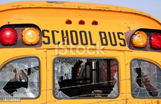 A close-up of the rear of an old school bus with broken windows and rusting paint.