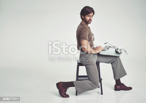 Studio shot of a 70's style businessman sitting on a stool using a typewriter