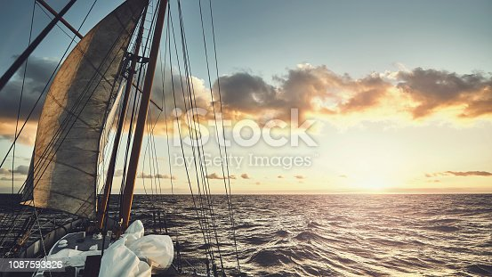 Old schooner sailing at sunset, travel and adventure concept, color toned picture.