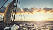 Old schooner sailing at sunset.