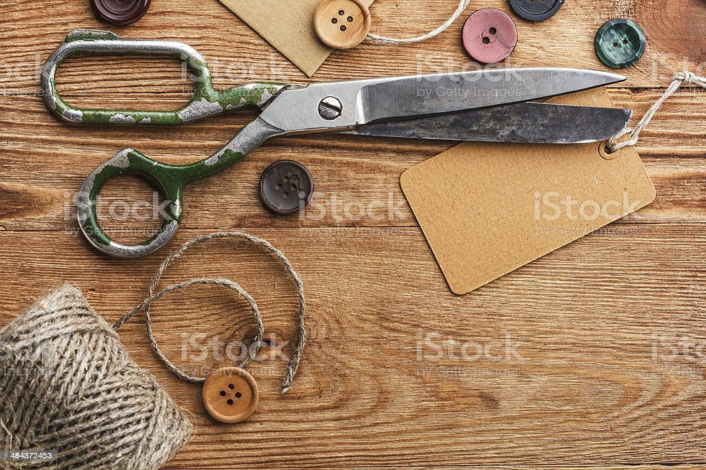 Old scissors and buttons on the wooden table stock photo